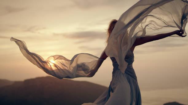 wind zu fangen. frau im eleganten kleid posiert in bergen - abendkleid lang blau stock-fotos und bilder