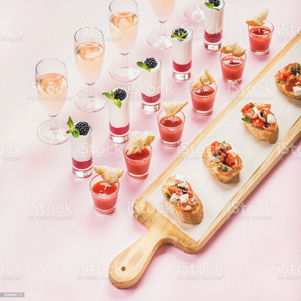 Catering, banquet food concept over pastel pink background stock photo