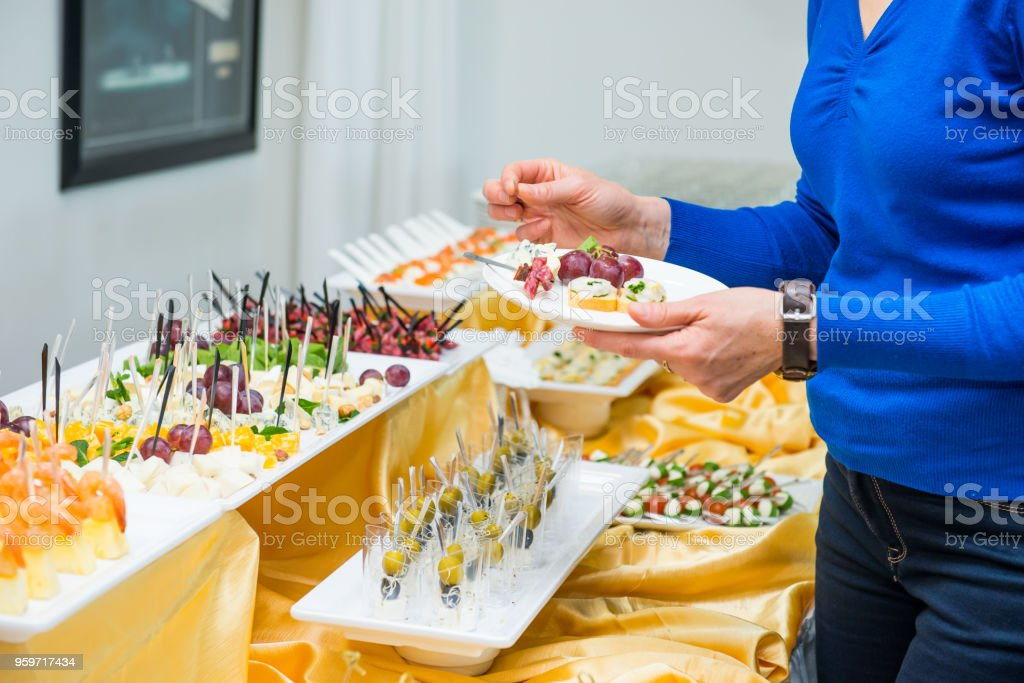 Catering buffet table with food and snacks for guests of the event. Group of people in all you can eat. Dining Food Celebration Party Concept. Service at business meeting, weddings. Selective focus. stock photo