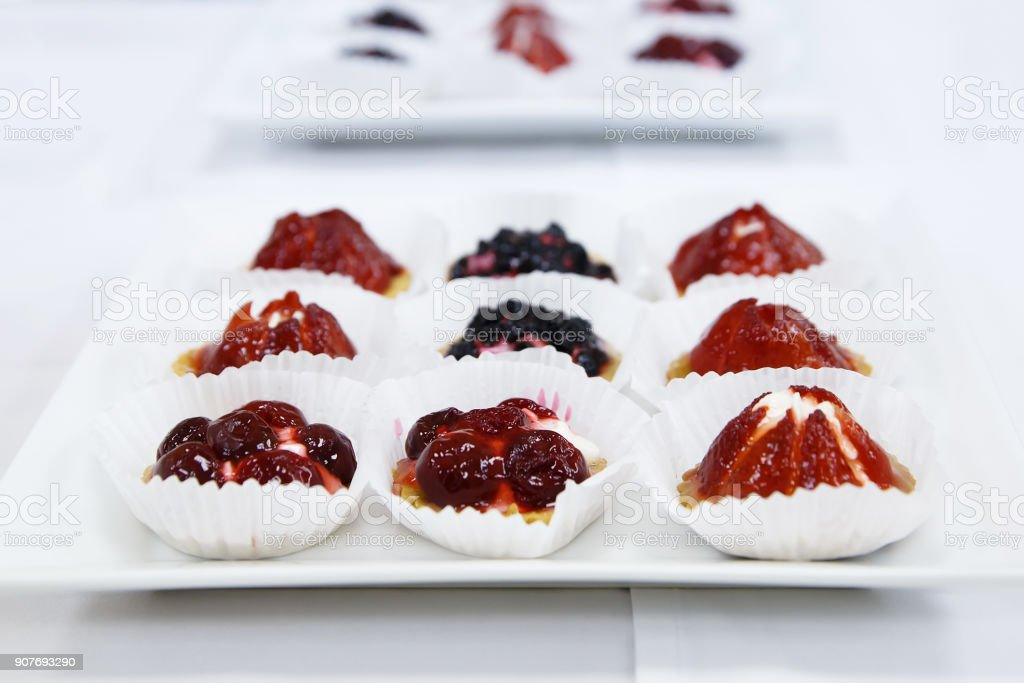 Catering sweet fruit and berry tarts dessert tray assorted stock photo