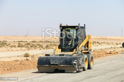 Tinghir, Morocco - September 24, 2019: Skid steer loader Caterpillar 216B2 at the interurban road.