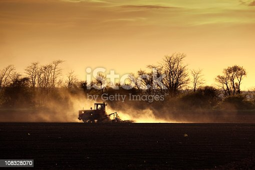Lonely tractor working on a field in spring, forming a cloud of dust.