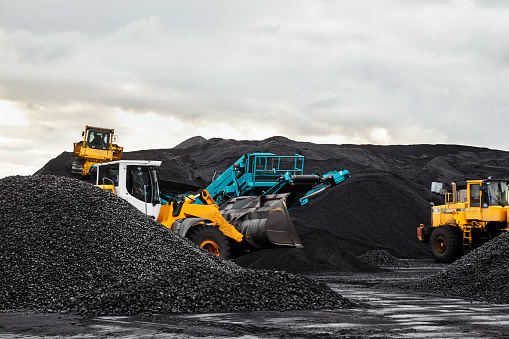 Caterpillar tractors collect black coal pile. Illustration of supply field of power station.