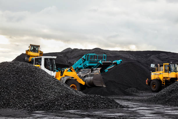 caterpillar tractors collect black coal pile. illustration of supply field of power station. - coal stock pictures, royalty-free photos & images