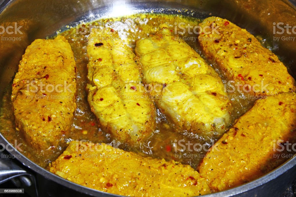 Catfish steaks marinated in Indian spices being fried in oil stock photo