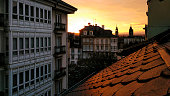 Cathedral and townscape in Lugo city, Galicia, Spain. Galería and slate rooftop in the foreground, traditional architectural features in Galicia. Dusk, sunset in the background.