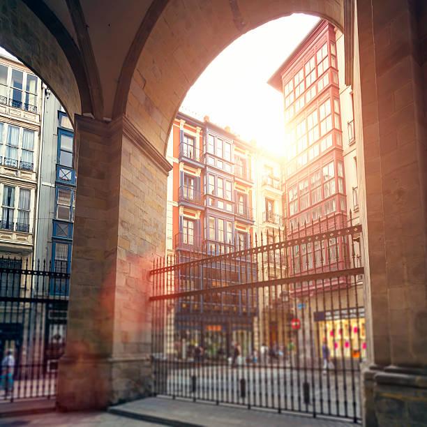 cathedral arches and multi colored facades in bilbao's casco viejo - walking home sunset street bildbanksfoton och bilder