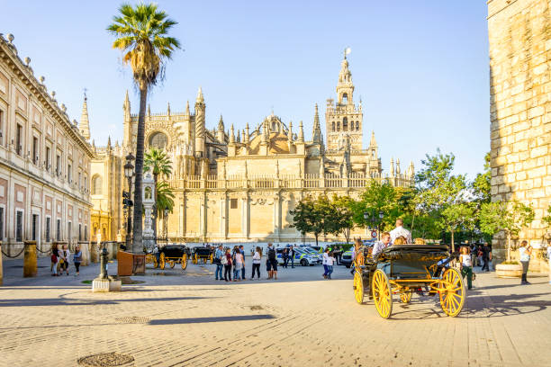 Cathedral of Saint Mary of the See with tourists, Seville, Spain Cathedral of Saint Mary of the See with horse carriage, Seville, Spain santa cruz seville stock pictures, royalty-free photos & images