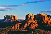 Famous Cathedral Rock formation and Courthouse Rock form at sunset Sedona Arizona USA.  House in foreground for perspective.  Snow in shaded areas.  High clouds after storm passes.  Red Rock country.  Or orange rock country.
