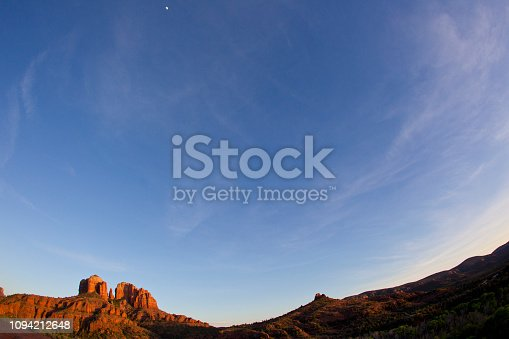 A view of Cathedral Rock in Sedona, Arizona, USA. The moon is visible at the top of the photo.