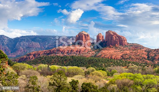 View to Cathedral Rock near Sedona with green bushes and trees in front and under a nicely clouded sky