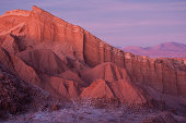 Unrecognizable people tourists watching sunset on rock formation mountain at ' Valle De La Luna ' in world famous Atacama desert in Chile - Adventure hiking trip to south latin america nature wonder