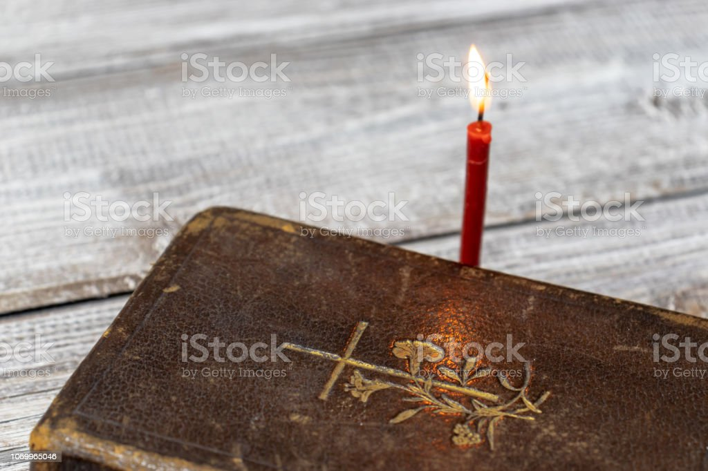 Catholic Bible And Red Church Burning Candle On Wooden