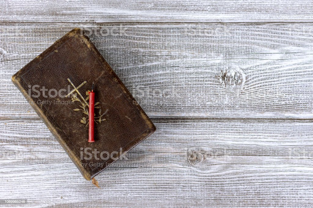 Catholic bible and red church nonflammable candle on wooden background with copy space stock photo