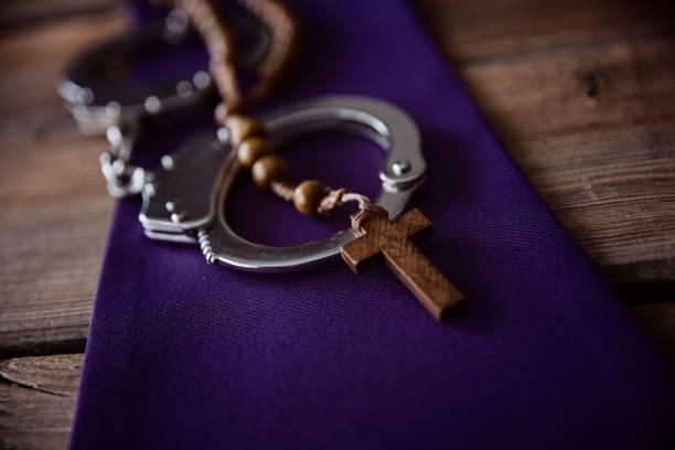 Katholische Kirchensymbole und Handschellen. – Foto