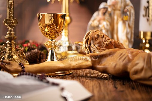 The Cross, monstrance, Jesus figure, Holy Bible and golden chalice on the rustic wooden table.