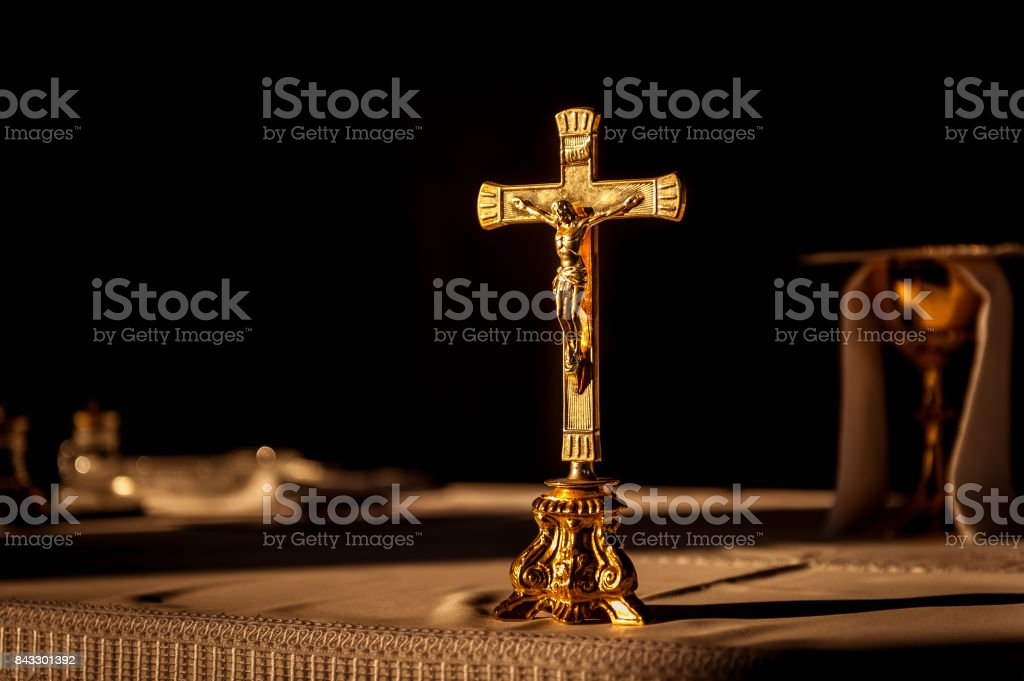Catholic cross on altar in church lit by sunlight stock photo