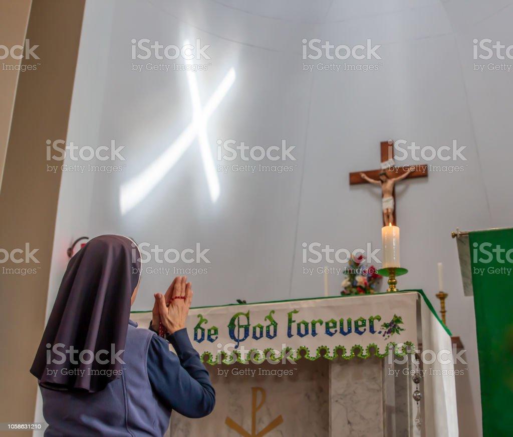 Freira católica, rezar o Rosário na frente do crucifixo com feixe de luz, criando uma cruz na parede. - foto de acervo