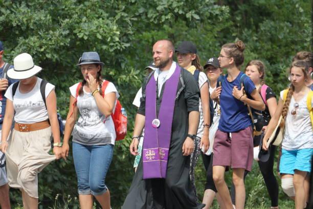 a catholic priest and other pilgrims walk on the road in samsonow, poland, during pilgrimage to the monastery of jasna gora in czestochowa, poland. - ferragosto foto e immagini stock