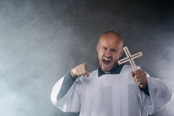 Catholic priest exorcist in white surplice and black shirt Catholic priest exorcist in white surplice and black shirt with cleric collar praying with crucifix the angry pastor stock pictures, royalty-free photos & images