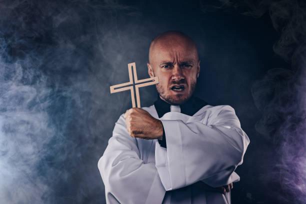 Catholic priest exorcist in white surplice and black shirt stock photo