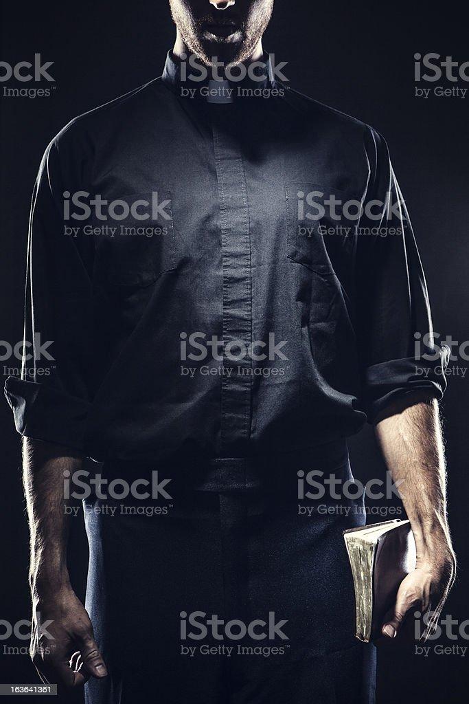 Catholic Priest Holding a Bible stock photo