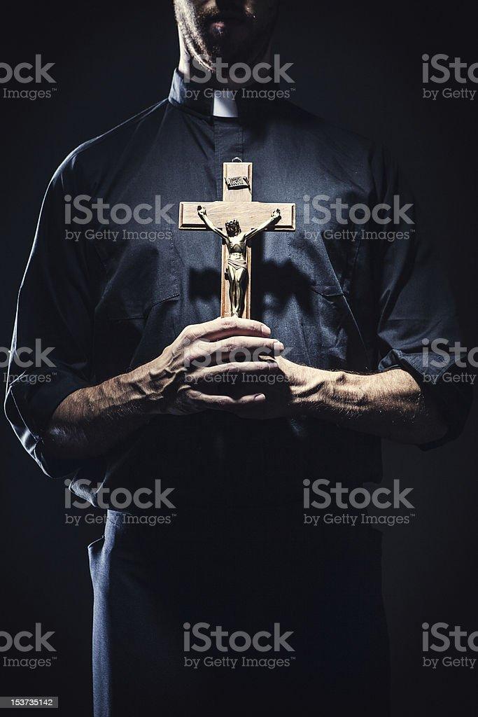Catholic Priest Holding a Wooden Crucifix stock photo