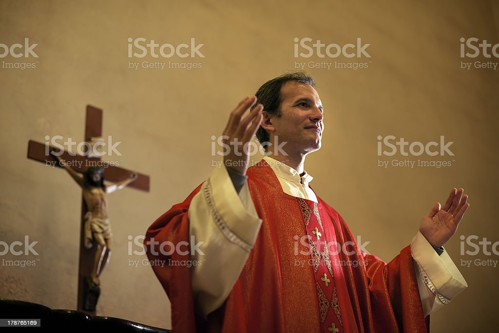Catholic priest on altar praying during mass stock photo