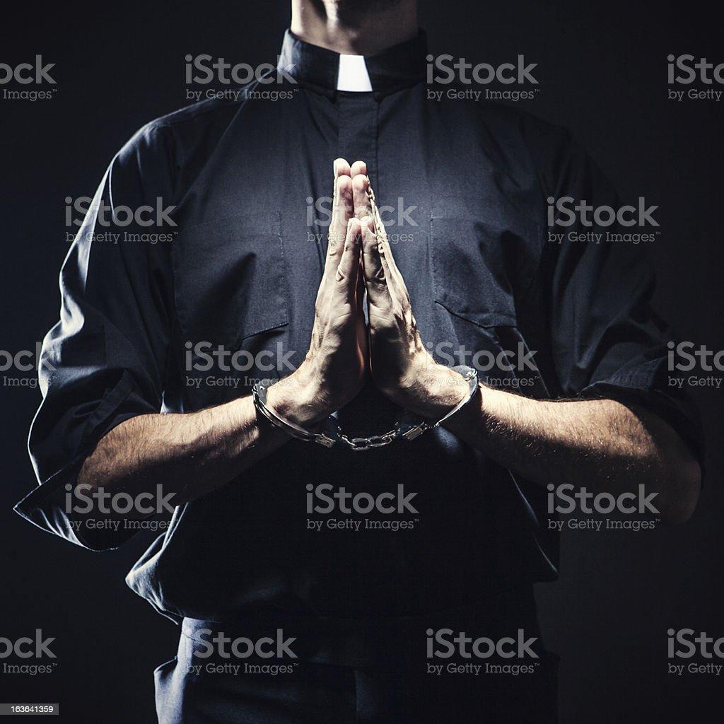 Catholic Priest Praying in Handcuffs stock photo