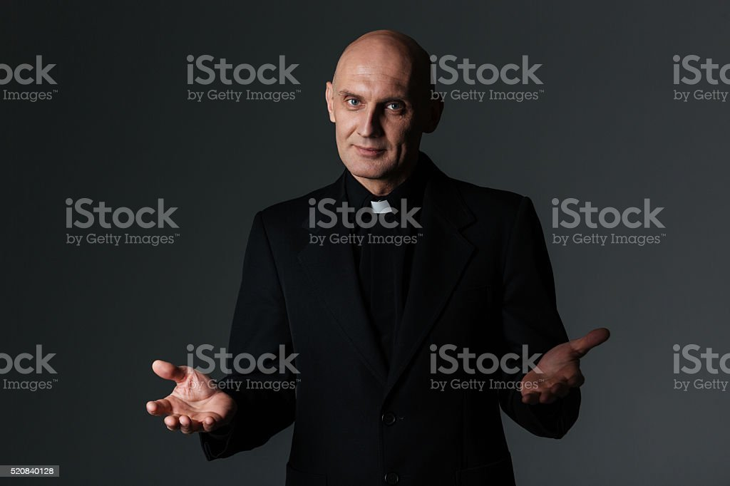 Catholic priest standing and doing welcome gesture stock photo