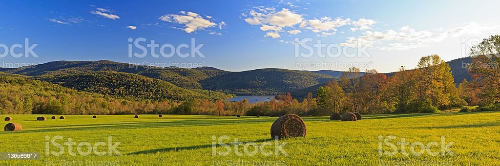Catskills Fall Panorama Panorama of a field of hay bales above the Pepacton Reservoir, surrounded by the Catskills Mountains of New York in the Autumn. Agricultural Field Stock Photo