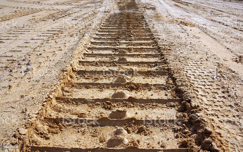 Catterpillar track in sand stock photo