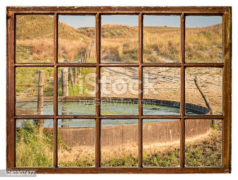 cattle drinking hole in a prairie of Nebraska Sandhills - fall morning scenery as seen from a vintage sash window