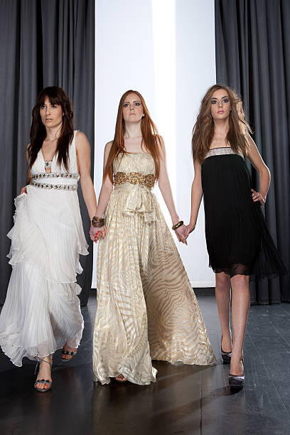 catwalk fashion show Three models holding hands and walking at a fashion show evening wear stock pictures, royalty-free photos & images