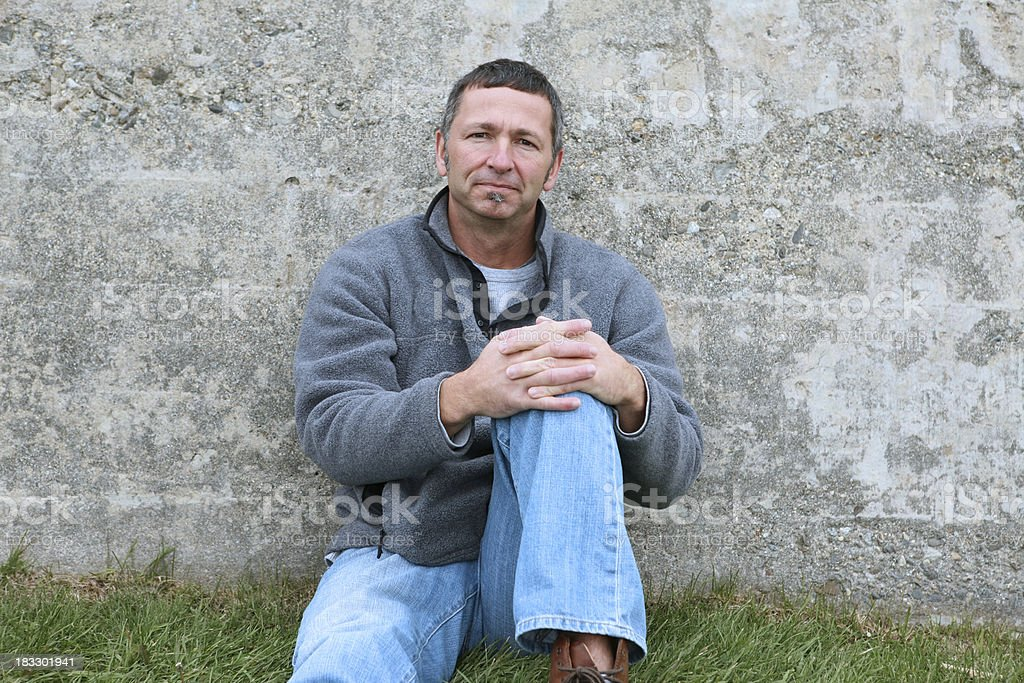 Caucasian 45 year old man leaning on a cement wall stock photo