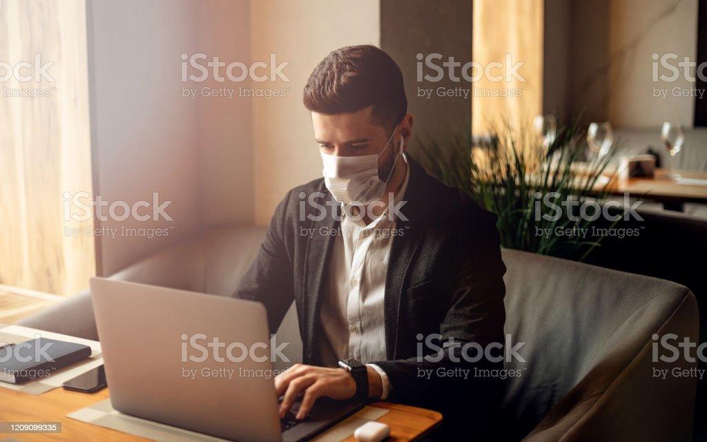 Hombre barbudo adulto caucásico en el café. Foto de concepto de estilo de vida con espacio de copia. Imagínate con un tipo guapo que usa máscara protectora. Retrato con portátil gris - Foto de stock de Negocio libre de derechos
