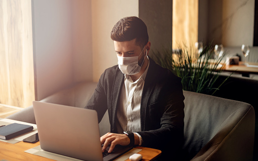 istock Caucasian adult bearded man indoors in cafe. Lifestyle concept photo with copy space. Picture with handsome guy who using protective face mask. Portrait with gray laptop 1209099335