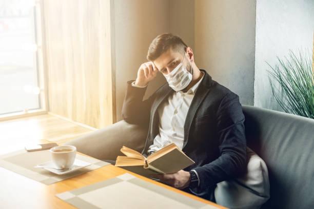 Kaukasier erwachsenen bärtigen Mann drinnen in Café. Lifestyle-Konzeptfoto mit Kopierraum. Bild mit schönen Kerl, der schützende Gesichtsmaske. Porträt mit Papierbuch – Foto
