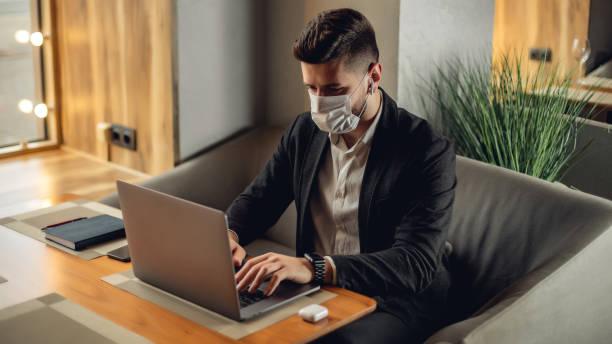 Kaukasier erwachsenen bärtigen Mann drinnen in Café. Lifestyle-Konzeptfoto mit Kopierraum. Bild mit schönen Kerl, der schützende Gesichtsmaske. Porträt mit grauem Laptop – Foto
