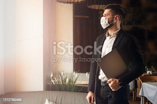 Caucasian adult bearded man indoors in cafe. Lifestyle concept photo with copy space. Picture with handsome guy who using protective face mask. Portrait with gray laptop