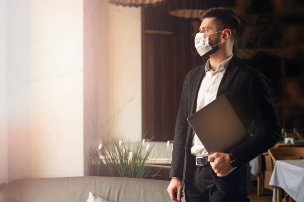 caucasian adult bearded man indoors in cafe. lifestyle concept photo with copy space. picture with handsome guy who using protective face mask. portrait with gray laptop - businessman covid mask foto e immagini stock