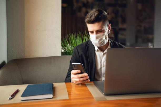 Kaukasier erwachsenen bärtigen Mann drinnen in Café. Lifestyle-Konzeptfoto mit Kopierraum. Bild mit stattlichen Kerl, der schützende Gesichtsmaske, Handy und Laptop verwenden – Foto