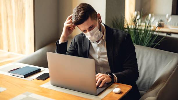 Kaukasier erwachsenen bärtigen Mann drinnen in Café. Lifestyle-Konzeptfoto mit Kopierraum. Bild mit Gesichtsmaske, Notebook und Laptop – Foto