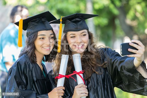 istock Caucasian and Hispanic college girls take selfie at graduation 615990340