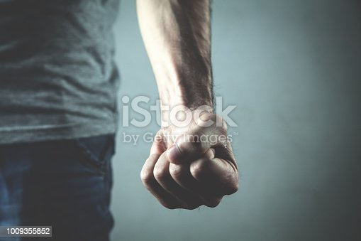 Caucasian angry and aggressive man threatening with fist.