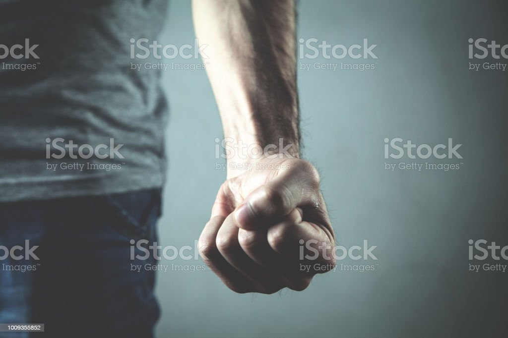 Caucasian angry and aggressive man threatening with fist. stock photo