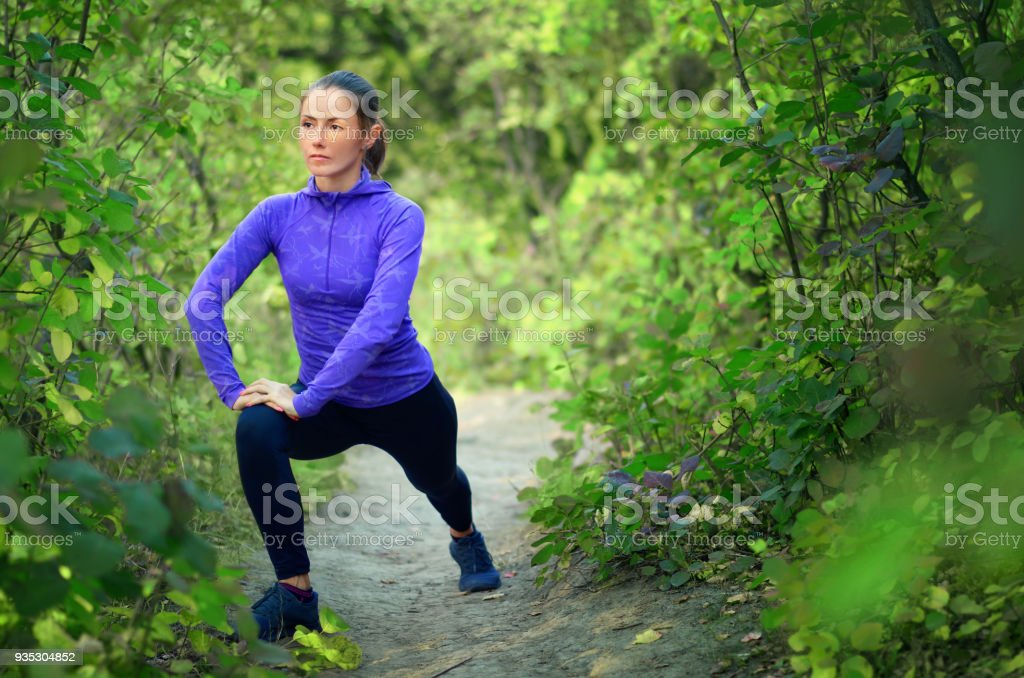 caucasian athletic girl in blue shirt and black sports leggins performs warming-up with legs  before jogging on a colorful green forest bac stock photo