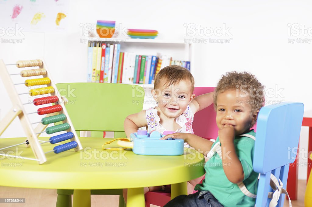 Caucasian Baby Girl Smiling During Playtime In A Nursery Setting royalty-free stock photo