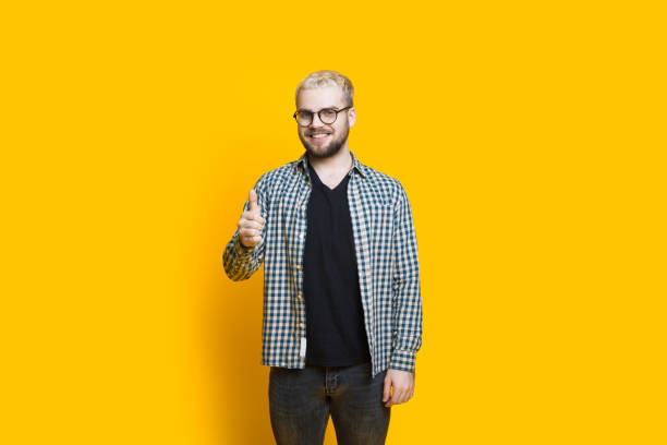 Caucasian bearded man with eyeglasses and blonde hair is gesturing the approbation sign in a yellow wall Caucasian bearded man with eyeglasses and blonde hair is gesturing the approbation sign in a yellow wall approbation stock pictures, royalty-free photos & images