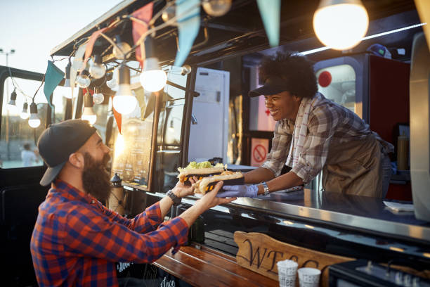 caucasian beardy hipster taking two sandwiches from polite female afro-american employee in fast food service stock photo